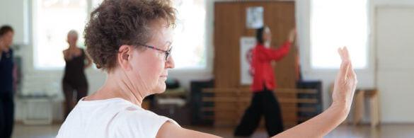 Seniorin macht eine Qigong-Übung