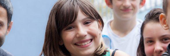 Ein Kind lächelt freundlich in die Kamera.