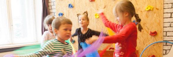 4 Kinder tanzen vor einer Kletterwand mit Tüchern