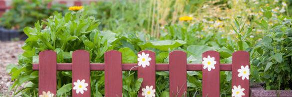 kleiner roter Zaun vor Blumenbeet