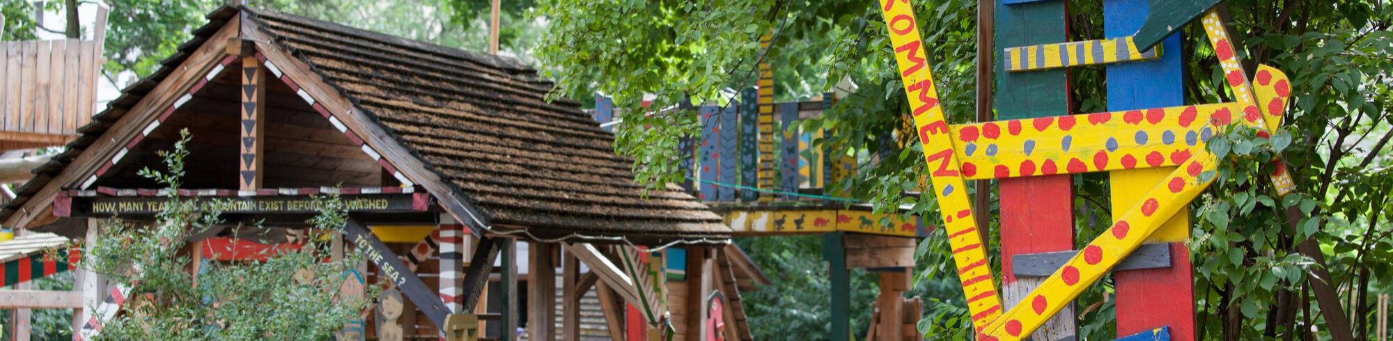 Hütte des Abenteuerspielplatzes mit Schild im Vordergrund