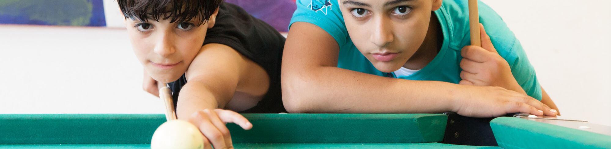 zwei Kinder spielen Billiard