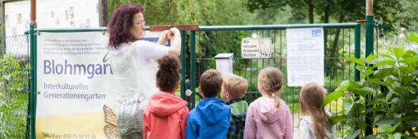 Kinder stehen vor einem Zaun