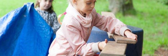 Kind baut mit Holz eine Brücke