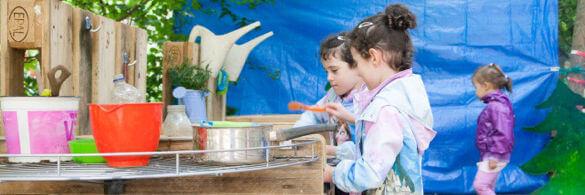 Kinder spielen im Garten mit Töpfen