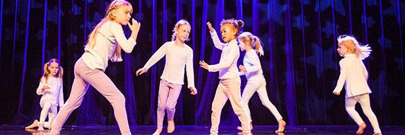 Kinder tanzen auf der Bühne. Sie tragen weiße Oberteile. Ihre Hosen sind rosa. Der Hintergrund ist dunkelblau.