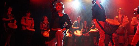 Percussion Gruppe bei einer Show auf einer Bühne. Die Beleuchtung lässt alle im Rot erstrahlen.