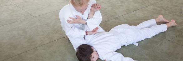 Ein Kind hält ein anderes mit Aikido-Griff am Boden.