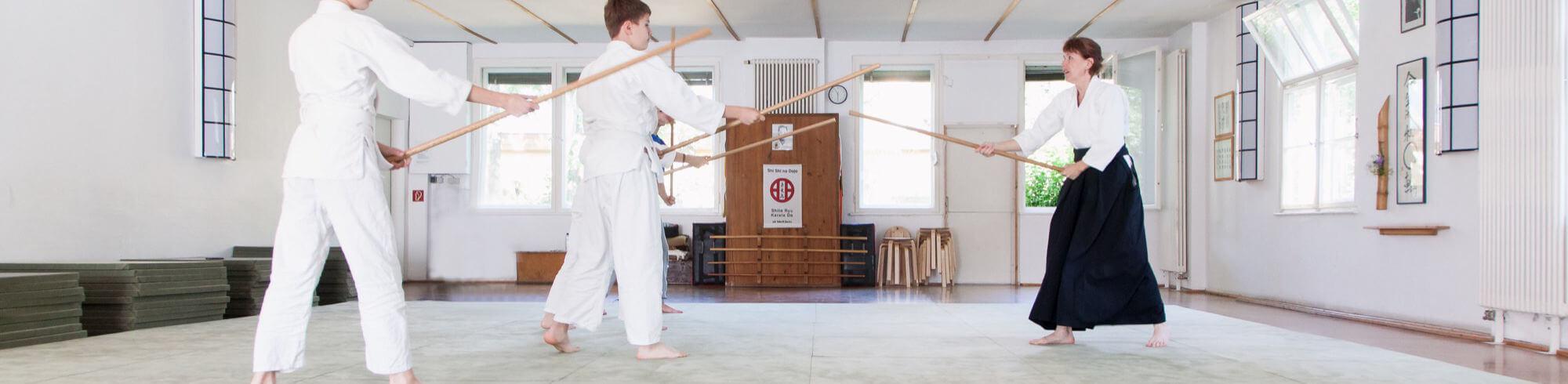 aikido für kinder. Kinder habe lange BO-Stöcke in der Hand