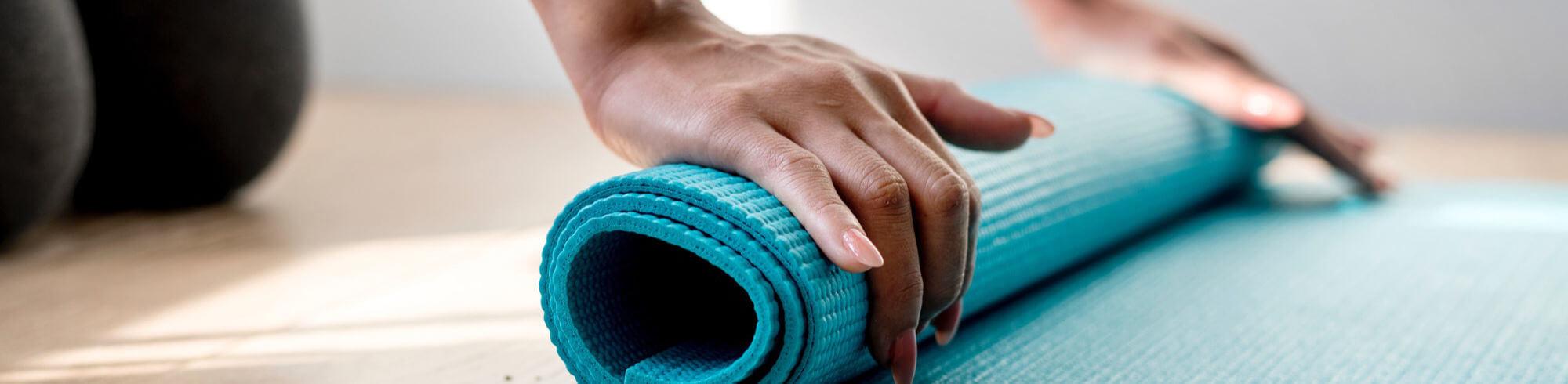 Zwei Händer dunkler Hautfarbe rollen eine türkis-farbende Yogamatte aus.