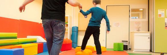 Kind balaciert mit Erwachsenem an der Hand durch einene Bewegungsparcour