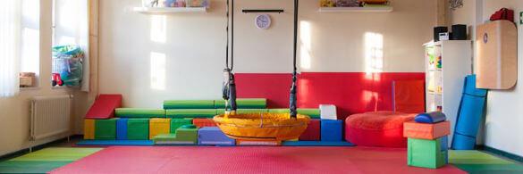 Gruppenraum im Familienzentrum Lichtenrade mit großer Schaukel in der Mitte. Im Hintergrnd sind bunten Spielelemente.