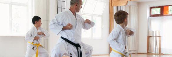 Zwei Kinder mit Karate-Lehrer