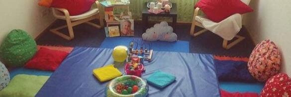 Ein Spielraum mit vielem bunten Spielzeug am Boden.