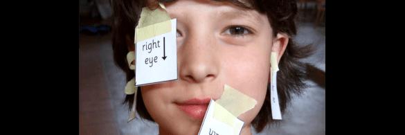 Junge hat Klebzettel mit englischen Worten im Gesicht