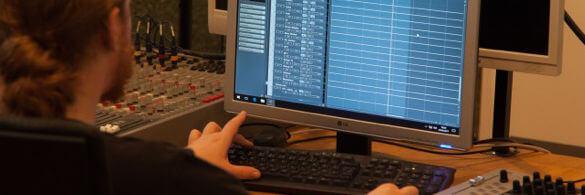 Eine Person edititiert Musik an einem PC