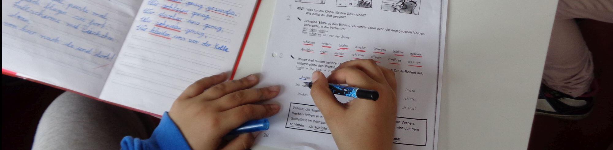 ein Schulheft und eine schreibende Kinderhand sind von oben zu sehen