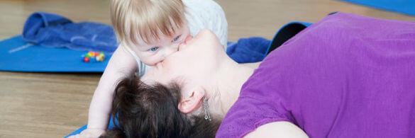 Eine Mutter liegt am Boden und ihr Babydrück sein Gesucht auf das ihre.