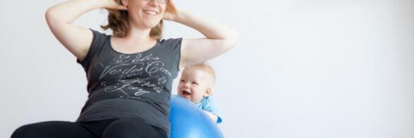 Eine Mutter sitzt auf einem Gymnastik-Ball und ihr Kleinkind steht da hinter uns lacht.