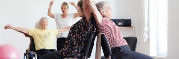 Zwei ältere Damen sitzen Rücken und Rücken auf dem Stuhl und heben die Arme