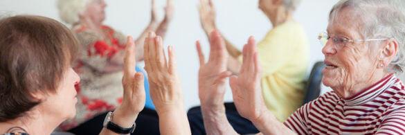 Zwei ältere Damen sind sich gegenüber und halten die Handflächen zu einander- Zum Anklatsch bereit.