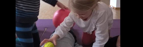 Ein Kind rollt mit einem Tennisball einem anderen über den Rücken.