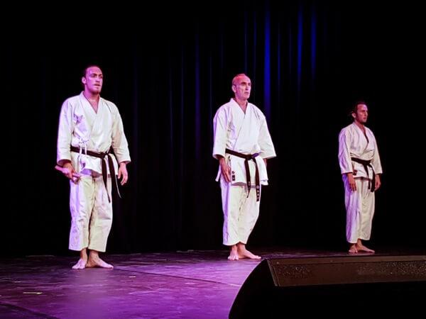 Drei Menschen stehen auf der Bühne. Sie tragen Karateanzüge. Sie stehen aufrecht. Die Arme liegen eng am Körper.