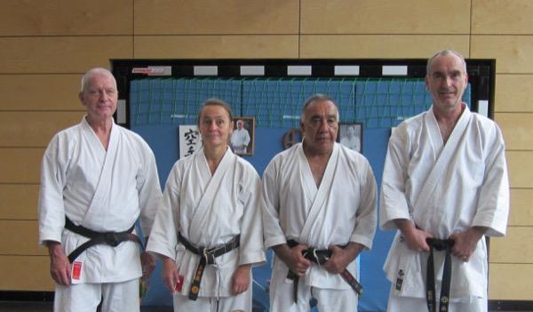 Mehrere Personen stehend und kniend in weißen Karateanzügen