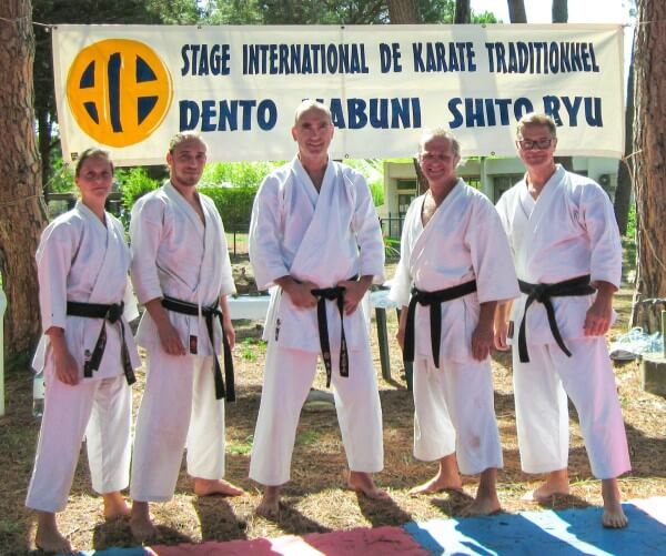 Fünf Meneschen in Karate-Anzügen stehen vor einem Plakat