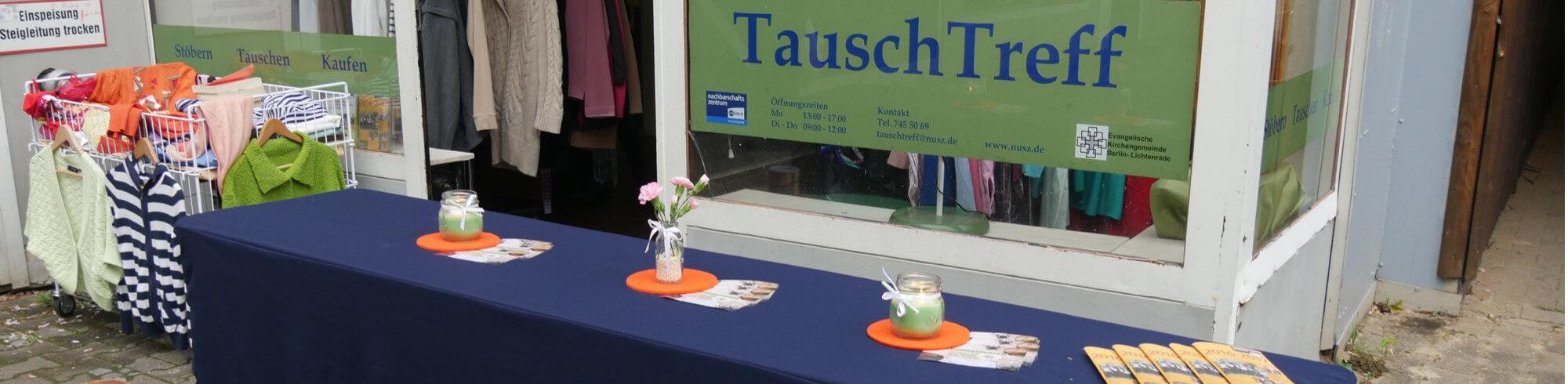 Vor dem Laden steht ein Tisch mit blauer Tischdecke. Im Hintergrund ein kleiner Laden mit großen Fenster.