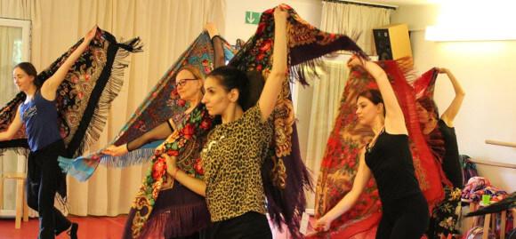 Mehrere Menschen tanzen einen romanischen Volkstanz. Sie haben schöne Tücher in den Händen