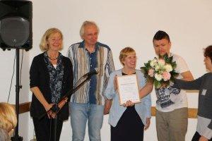 Sigrid Zwicker, Hinrich Scheffens, Renate Wilkening und ein Gebärdendolmetscher stehhen auf der Bühne